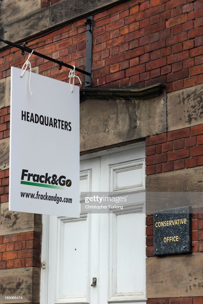A sign reading 'Headquarters Frack Go' placed by Greenpeace campaigners protesting against gas fracking hangs outside the constituency office of...