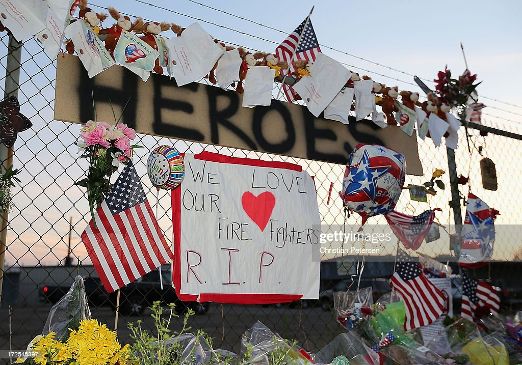 A sign reading 'Heroes' is displayed on a fence, adorned with mementos, outside of Station 7 on July 3, 2013 in Prescott, Arizona. Nineteen firefighters based out of Station 7 died battling a fast-moving wildfire near Yarnell, Arizona on June 30. Station 7 has been the home of the Granite Mountain Interagency Hotshot Crew since 2010.