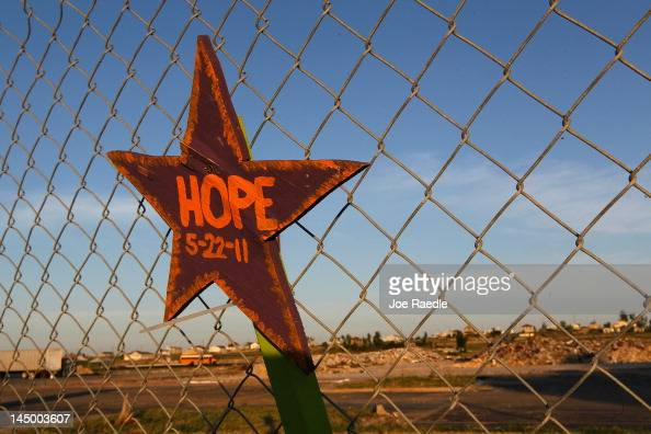 A sign reading 'Hope' is seen on a fence around the rubble of the Joplin High School after one year ago today the town was hit by a catastrophic...