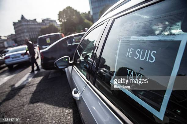 A sign reading Je Suis Taxi sits in a rear passenger window of a taxi as French cab drivers protest against Uber Technologies Inc's car sharing...