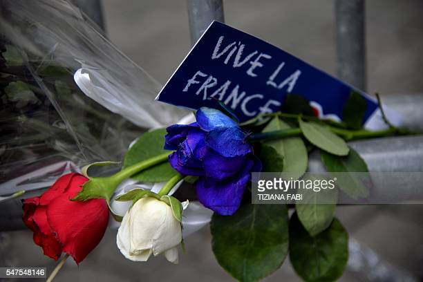 TOPSHOT A sign reading 'Long live France' is placed near roses in the colors of the French flag at a makeshift memorial in front of the French...