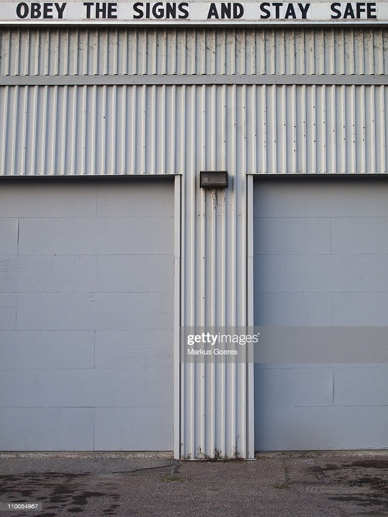A sign reading OBEY THE SIGNS AND STAY SAFE atop a warehouse building