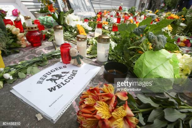 A sign reading 'Refugees Welcome' is placed among flowers and candles at a makeshift memorial for the victims of a knife attack on July 30 2017 in...