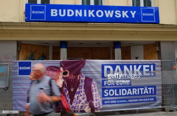 A sign reading 'Thanks for you solidarity we are soon back for you' is seen at a fence in front of the Budnikowsky shop after it has been damaged...