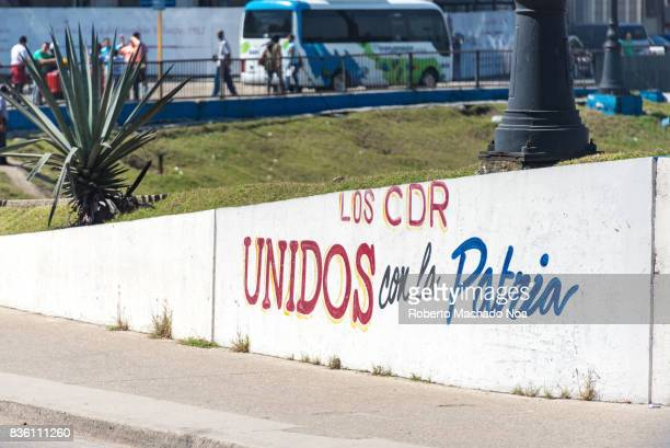 sign reading United to the Homeland' Red and blue Spanish text written on slanting low wall of a public park