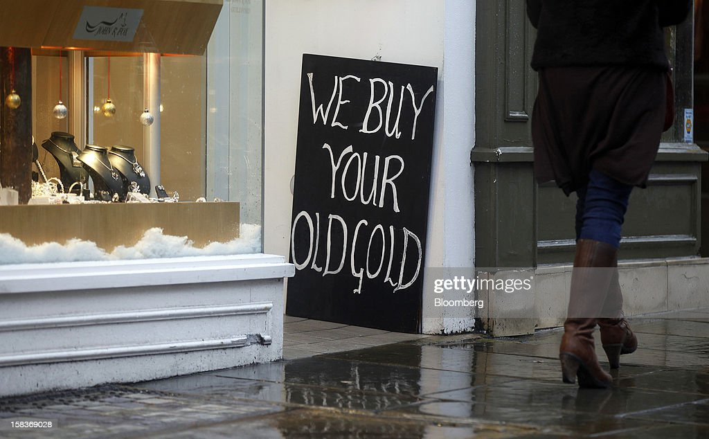 A sign reading 'We Buy Your Gold' sits outside a jewelry store in Guildford, U.K., on Friday, Dec. 14, 2012. Standard & Poor's lowered its outlook on Britain's top credit rating to negative, citing weak economic growth and a worsening debt profile. Photographer: Simon Dawson/Bloomberg via Getty Images