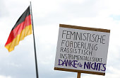 A sign reads 'Racist Use of Feminist Demands Thanks for Nothing' in German in front of a German flag during a demonstration against sexual violence...