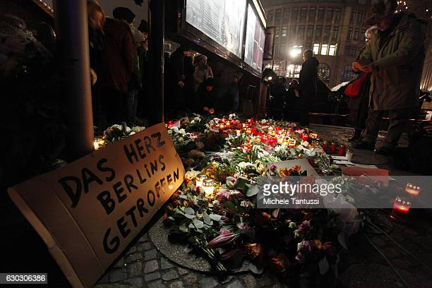 A sign reads 'the heart of Berlin has been hit' as people leave flowers and candles at the area after a lorry truck ploughed through a Christmas...