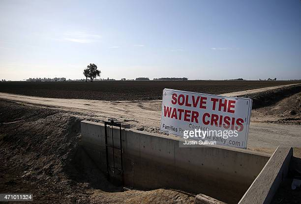 A sign referencing the drought is posted next to a fallow field on April 24 2015 in Lemoore California As California enters its fourth year of severe...