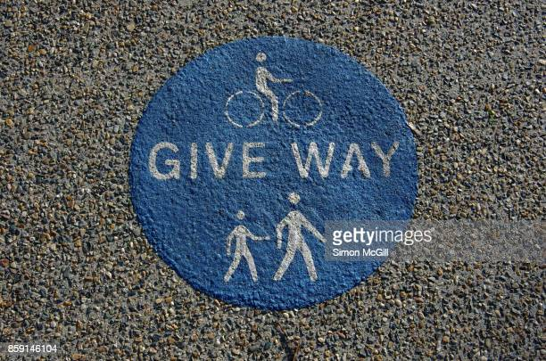 Sign reminding cyclists to give way to pedestrians on a shared pedestrian and cycling path in Canberra, Australian Capital Territory, Australia