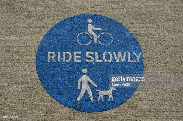 Sign reminding cyclists to ride slowly in consideration of dog walkers on a shared pedestrian and cycling path in Canberra, Australian Capital Territory, Australia