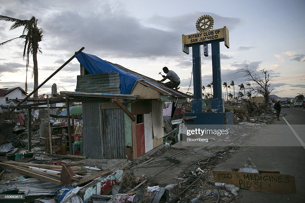 A sign requests food and medicine as a man repairs the roof of a shack in Tacloban, the Philippines, on Monday, Nov. 18, 2013. Super Typhoon Haiyan slammed into the central Philippines on Nov. 8, knocking down most buildings, killing thousands, displacing 4 million people and affecting more than 10 million. Photographer: Paula Bronstein/Bloomberg via Getty Images
