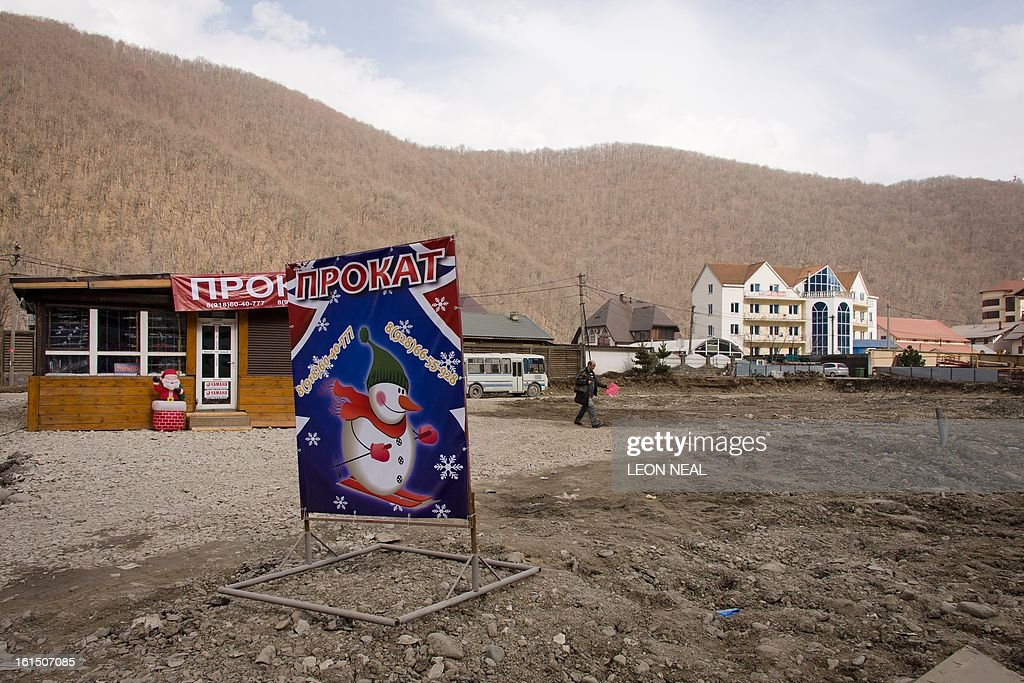 A sign showing a skiing snowman stands in the middle of a snow-free Krasnaya Polyana close to Sochi 2014 Olympic venues some 50 km of the Black Sea resort of Sochi, on February 11, 2013. With a year to go until the Sochi 2014 Winter Games, construction work continues as tests events and World Championship competitions are underway. AFP PHOTO / LEON NEAL