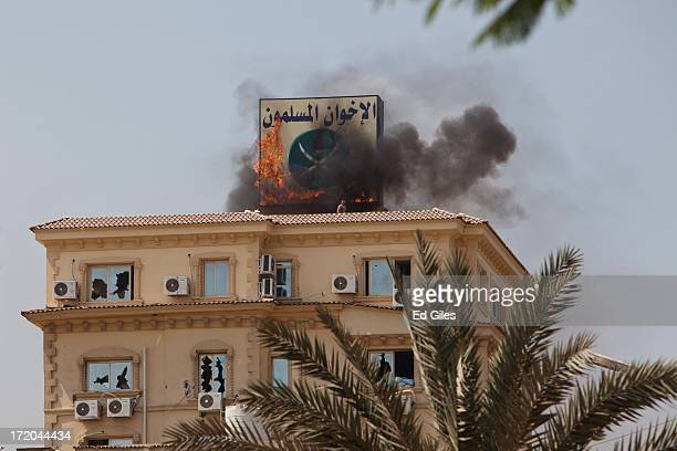 A sign showing the logo of the Muslim Brotherhood burns on the roof of the headquarters of Egypt's Muslim Brotherhood as protesters ransack the...