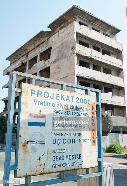 A sign shows a reconstruction project in front of a derelict building damaged by bulletts from the 1993 war as the city of Mostar remembers the 1993...