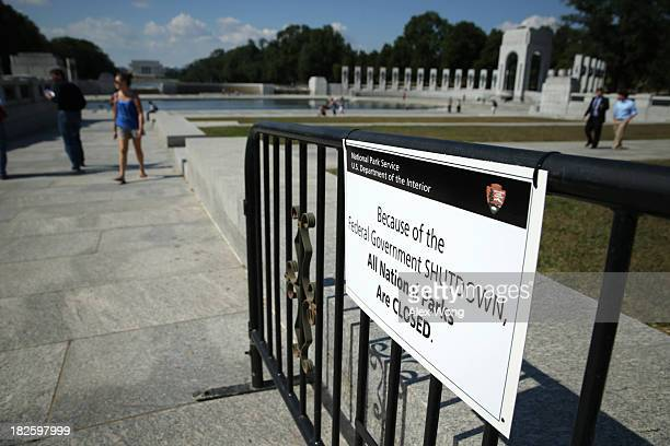 A sign shows that the World War II Memorial is closed during a government shutdown is hung at its entrance October 1 2013 in Washington DC The...