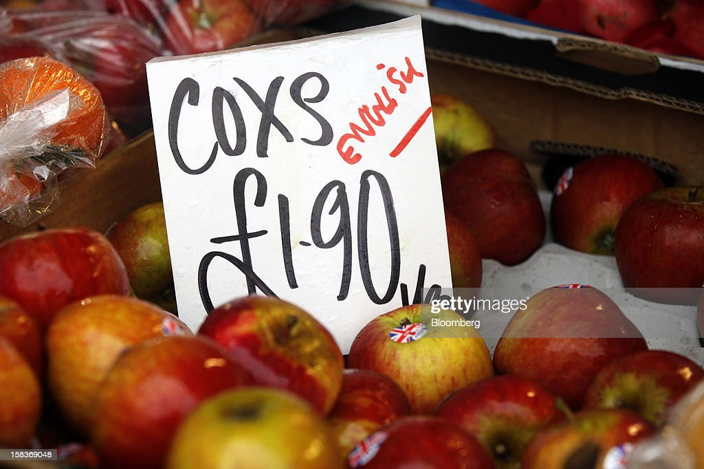 A sign shows the price in pounds of English Cox apples displayed for sale on a fruit and vegetable stall at a market in Guildford, U.K., on Friday, Dec. 14, 2012. Standard & Poor's lowered its outlook on Britain's top credit rating to negative, citing weak economic growth and a worsening debt profile. Photographer: Simon Dawson/Bloomberg via Getty Images