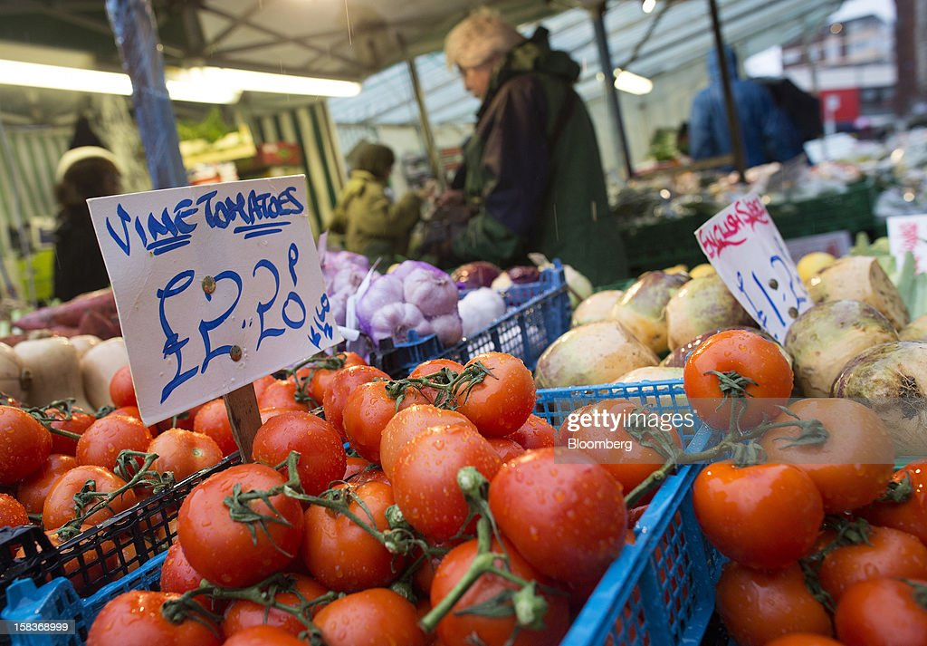 A sign shows the price in pounds of tomatoes displayed for sale on a fruit and vegetable stall at a market in Guildford, U.K., on Friday, Dec. 14, 2012. Standard & Poor's lowered its outlook on Britain's top credit rating to negative, citing weak economic growth and a worsening debt profile. Photographer: Simon Dawson/Bloomberg via Getty Images
