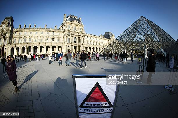 A sign shows the symbol of France's national security alert system 'Vigipirate' set at the highest 'Attack alert' level near the Louvre Pyramid in...