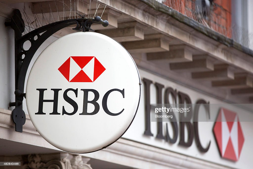 A sign sits above a HSBC bank, operated by HSBC Holdings Plc, in Godalming, U.K., on Monday, Aug. 3, 2015. HSBC, Europe's largest bank, reported an 18 percent climb in second-quarter profit amid higher trading income and gains from a sale of shares in China's Industrial Bank Co. Photographer: Jason Alden/Bloomberg via Getty Images