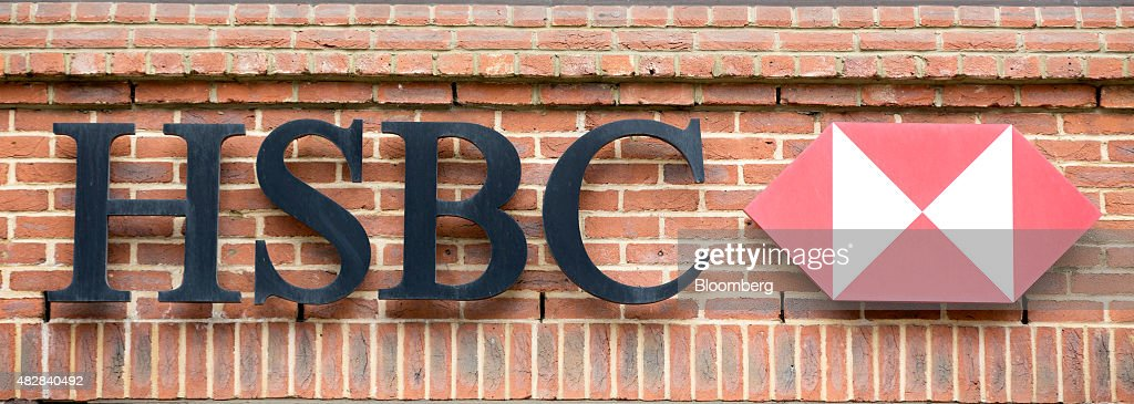 A sign sits above a HSBC bank, operated by HSBC Holdings Plc, in Guildford, U.K., on Monday, Aug. 3, 2015. HSBC, Europe's largest bank, reported an 18 percent climb in second-quarter profit amid higher trading income and gains from a sale of shares in China's Industrial Bank Co. Photographer: Jason Alden/Bloomberg via Getty Images