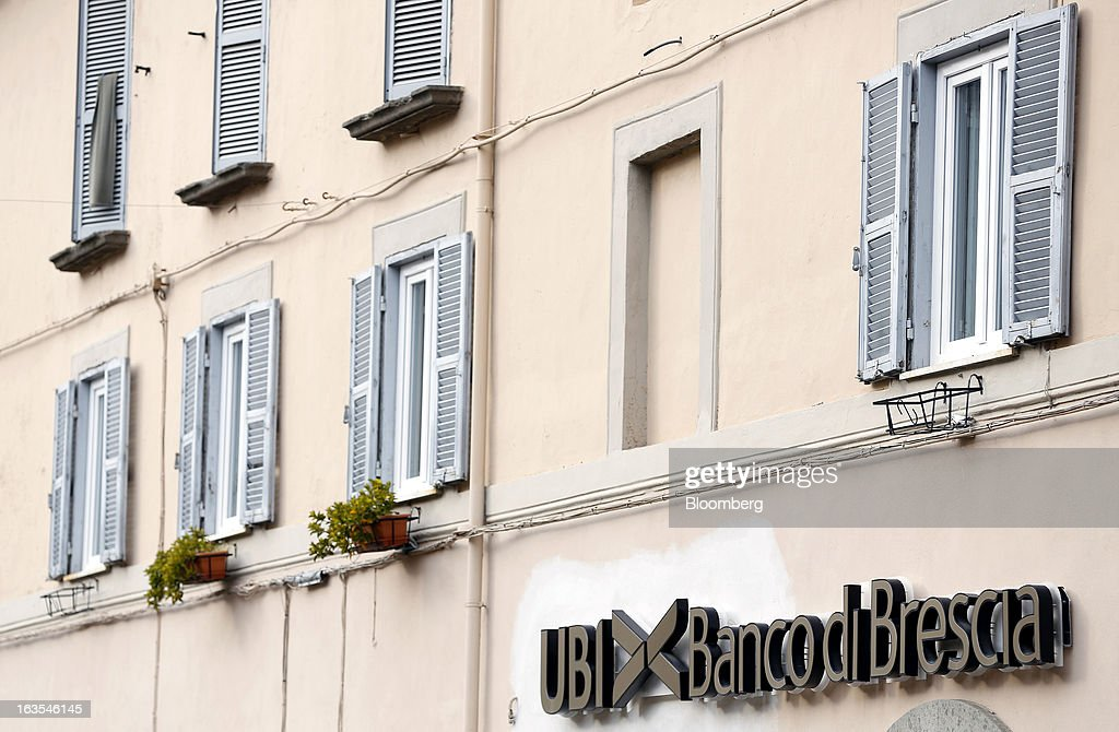 A sign sits above the entrance to a Banco di Brescia bank branch, a subsidiary of Unione di Banche Italiane SCPA (UBI Banca), in Vetralla, Italy, on Monday, March 11, 2013. Intesa Sanpaolo SpA and UniCredit SpA are among Italian banks due to report losses for the fourth quarter this week, as the economic contraction meant more clients failed to repay their debts. Photographer: Alessia Pierdomenico/Bloomberg via Getty Images