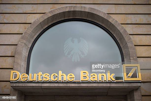 A sign sits above the entrance to a Deutsche Bank AG branch in Frankfurt Germany on Thursday Oct 29 2015 Deutsche Bank AG said it will shrink the...