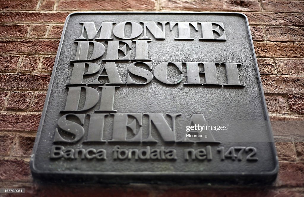 A sign sits on a wall outside a Banca Monte dei Paschi di Siena SpA bank branch in Siena, Italy, on Monday, April 29, 2013. An Italian judge rejected a request by prosecutors to seize as much as 1.95 billion euros ($2.5 billion) of assets held by Nomura Holdings Inc. as they probed how Banca Monte dei Paschi di Siena SpA used derivatives to conceal losses. Photographer: Alessia Pierdomenico/Bloomberg via Getty Images