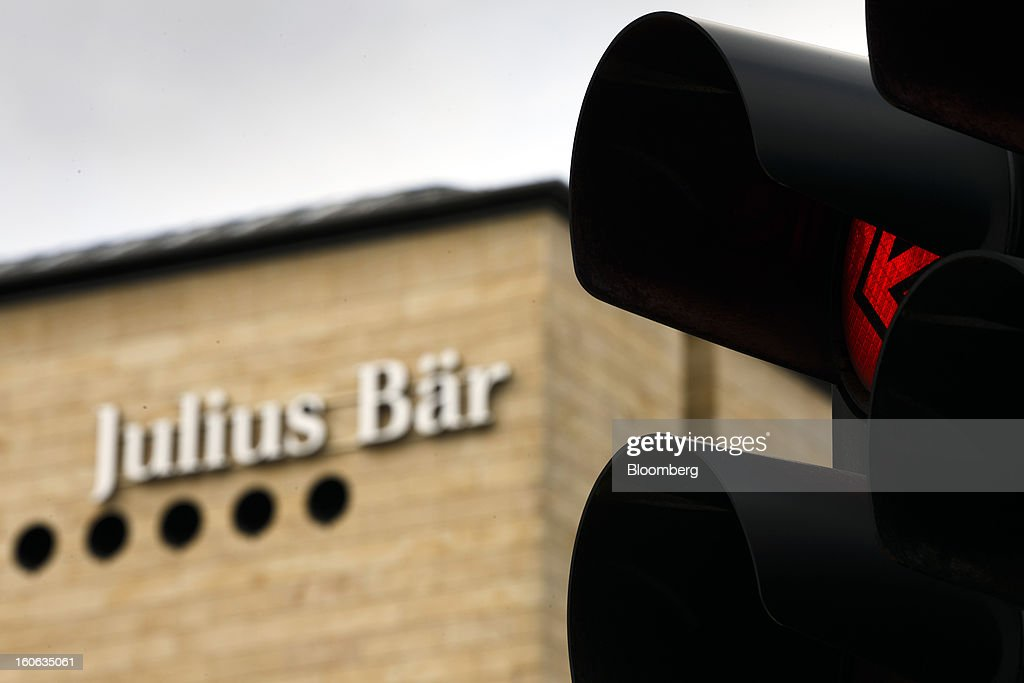 A sign sits on a wall outside the offices of Julius Baer Group Ltd., near an illuminated traffic signal, in Geneva, Switzerland, on Sunday, Feb. 3, 2013. Julius Baer Group Ltd., the third-largest Swiss wealth manager, reported declining revenue margins on assets under management as full-year profit matched analyst estimates. Photographer: Valentin Flauraud/Bloomberg via Getty Images