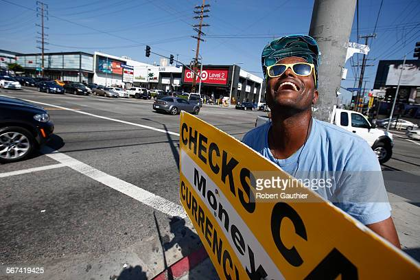 LOS ANGELES CA FRIDAY MARCH 14 2014 Sign spinner David Harwell grabs attention by dancing and holding an arrow shaped cardboard sign advertising a...