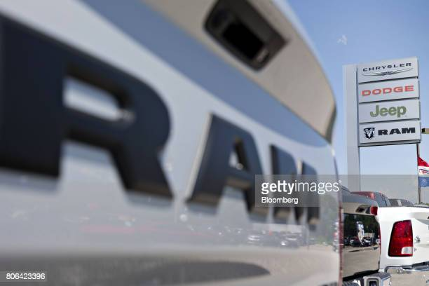 A sign stands near a row of Fiat Chrysler Automobiles Dodge Ram pickup trucks at a car dealership in Moline Illinois US on Saturday July 1 2017...