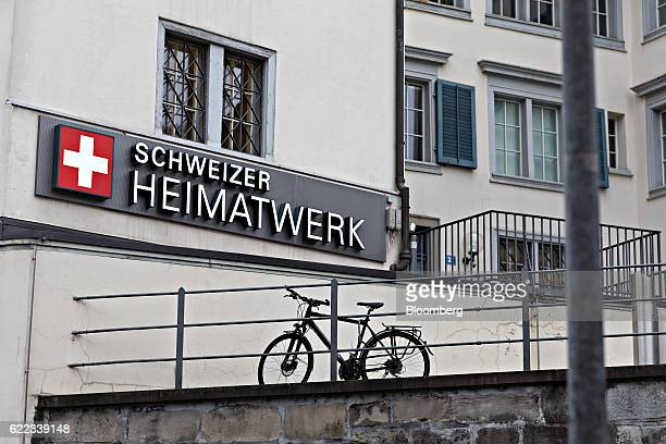 A sign stands on an exterior wall of the Schweizer Heimatwerk Genossenschaft craft and design retailer in Zurich Switzerland on Wednesday Nov 9 2016...