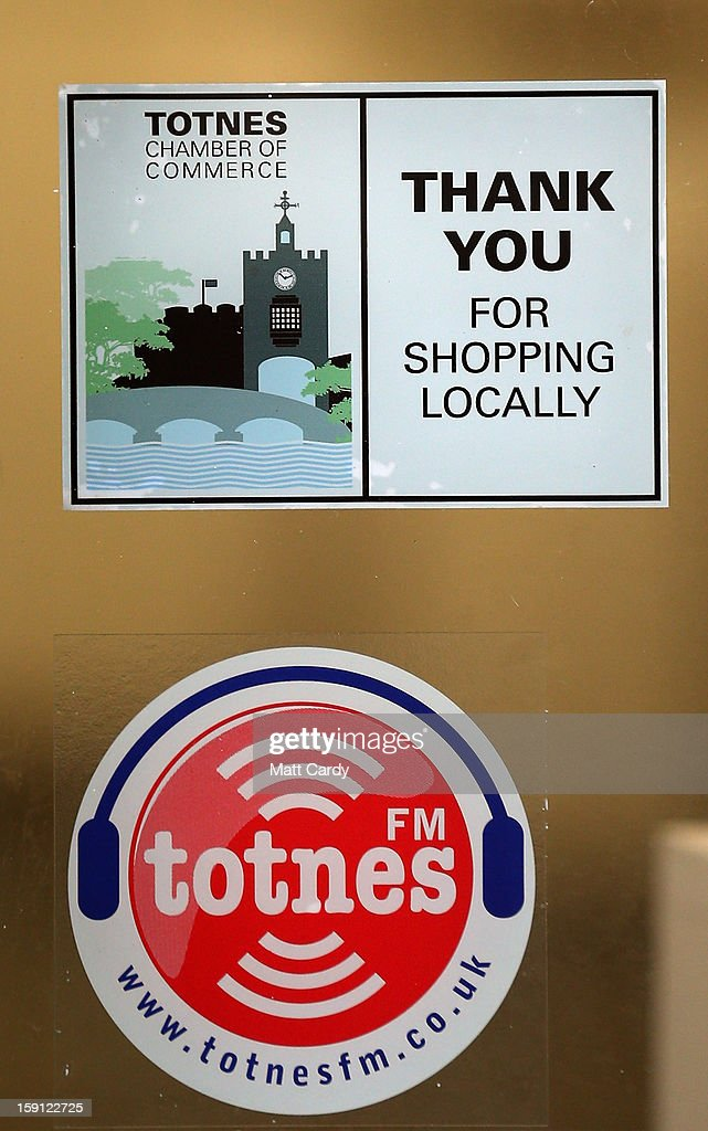 A sign thanking people for shopping locally is seen in a shop window along the main shopping street of Totnes on January 8, 2013 in Totnes, England. The Devon town is renowned for its belief in promoting trade of local independent retailers, famously denying the plans by national coffee chain Costa to open a high street branch in the town. Boasting its own local currency, Totnes has a shop vacancy rate of 6%, less than half than the national average, whilst 80% of outlets are independently owned.