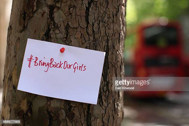 A sign that reads 'Bring back our girls' is pinned to a tree as Protesters calling for the release of a group of abducted Nigerian schoolgirls gather...