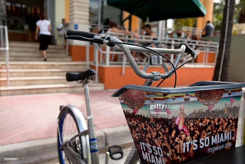 A sign that reads 'It's So Miami' is displayed on a rental bicycle in front of Starbucks Corp. coffee shop in the South Beach neighborhood of Miami Beach, Florida, U.S., on Wednesday, Feb. 20, 2013. U.S. exports in the travel and tourism sector reached $168.1 billion in 2012, up 10.1 percent from the year-ago level of $152.7 billion, according to data released Feb. 22 by the Commerce Department's International Trade Administration. Photographer: Ty Wright/Bloomberg via Getty Images