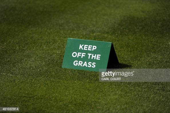 A sign that reads 'keep off the grass' is placed on freshly cut grass at The All England Tennis Club in Wimbledon southwest London on June 22 on the...