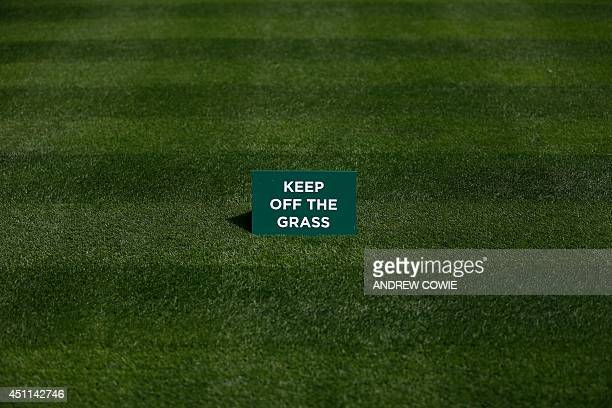 A sign that reads 'keep off the grass' is placed on freshly cut grass on day two of the 2014 Wimbledon Championships at The All England Tennis Club...