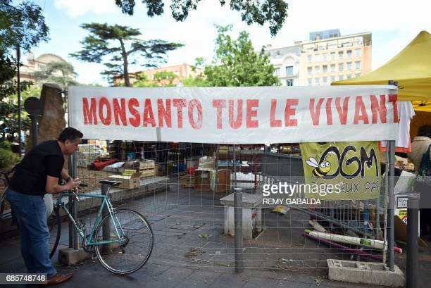 A sign that reads 'Monsanto kills life' refering to the agrochemical and agricultural biotechnology corporation hangs close to a supermarket as...