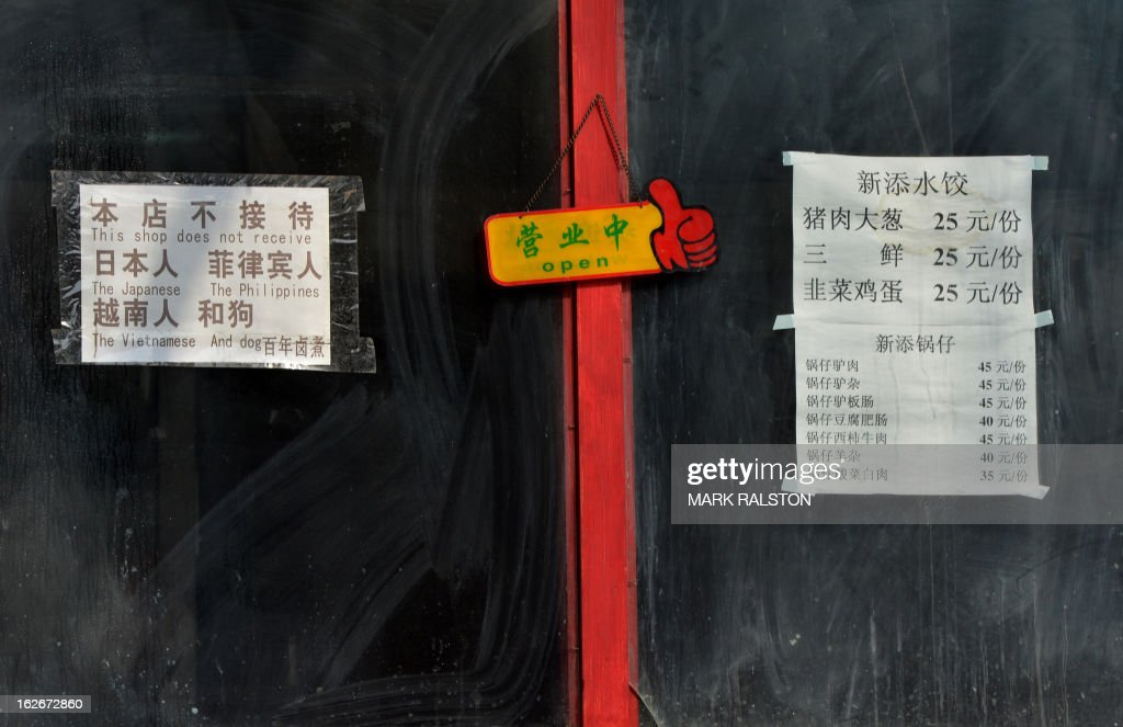 A sign (L) that reads 'This shop does not receive the Japanese, The Philippines, The Vietnamese and Dog' is displayed outside a restaurant in the historic tourist district of Houhai in Beijing on February 26, 2013. China is currently in border disputes with Japan, Vietnam and the Philippines and has grown increasingly assertive in recent years in claiming islands and waters even without effective control of them -- in some cases hundreds of kilometres from the Chinese mainland and close to rival claimants' coasts. AFP PHOTO/Mark RALSTON