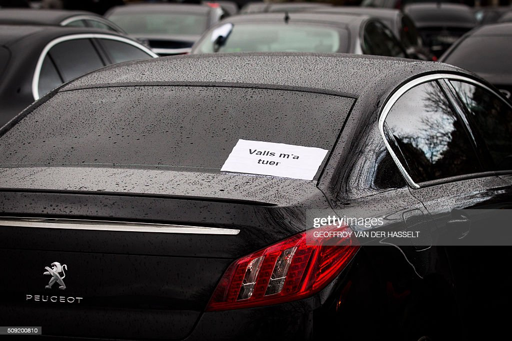 A sign that reads, 'Valls wants to kill me' refering to French Prime Minister Manuel Valls, is seen on the back window of a car as VTC vehicles block the roundabout at Place de la Nations to protest against the LOTI law in Paris, on February 9, 2016. Uber and other ride-hailing companies, known in France as 'voitures de tourisme avec chauffeur' (VTC) are a class of companies that allow passengers to book rides with independent professional chauffeurs, / AFP / Geoffroy Van der Hasselt