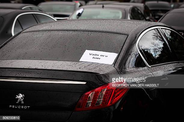 A sign that reads 'Valls wants to kill me' refering to French Prime Minister Manuel Valls is seen on the back window of a car as VTC vehicles block...