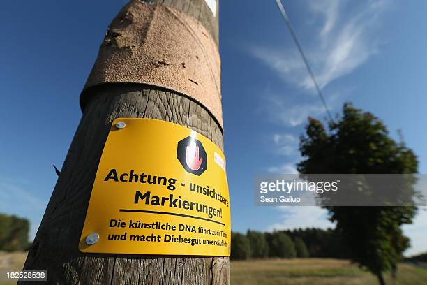 A sign that reads 'Warning invisible markation Artificial DNA leads to the culprit and makes stolen goods unsellable' hangs on a telephone pole on...