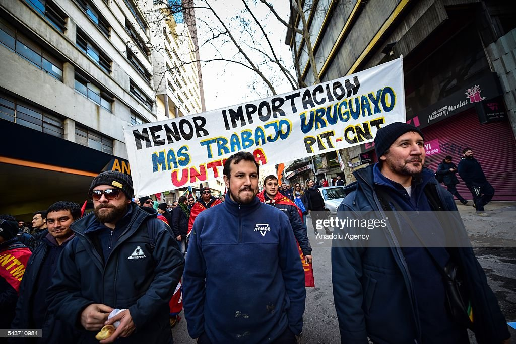 A sign that says 'LESS IMPORTING, MORE URUGUAYAN WORK ' in the march against the economic policies in Montevideo on June 29, 2016. The PIT-CNT (the only organization of unionized workers of Uruguay) today made a partial strike and marched to front the Ministry of Economy of Uruguay.