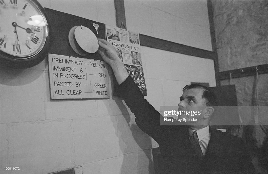 In an air raid control centre, a man puts up a red disc to signal that an air raid is imminent in the area, UK, July - August 1940. A sign under the disc lists the colour code for air raid status, yellow for preliminary standby, red for imminent and in progress, green for passed by and white for the all-clear. Original publication: Picture Post - 300 - Air Raid - pub. 17th August 1940.