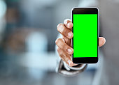 Closeup shot of an unrecognizable businessman holding up a cellphone with a green screen in an office