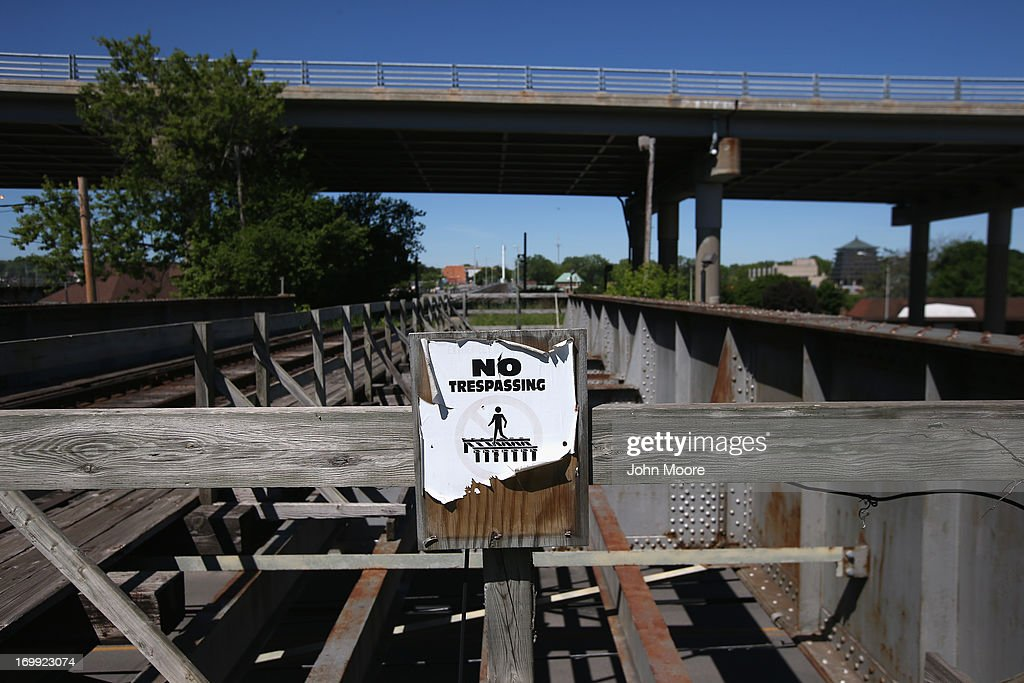 A sign urges pedestrians not to walk over a rail bridge connecting the U.S. with Canada on June 4, 2013 near Black Rock, New York. U.S. Border Patrol agents monitor the bridge for undocumented immigrants trying to cross either into or out of the United States illegally on the bridge.
