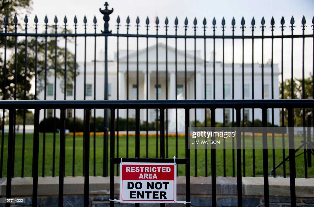 A sign warning of a restricted area is posted on the temporary barricade in front of the fence line to the White House in Washington DC October 23...