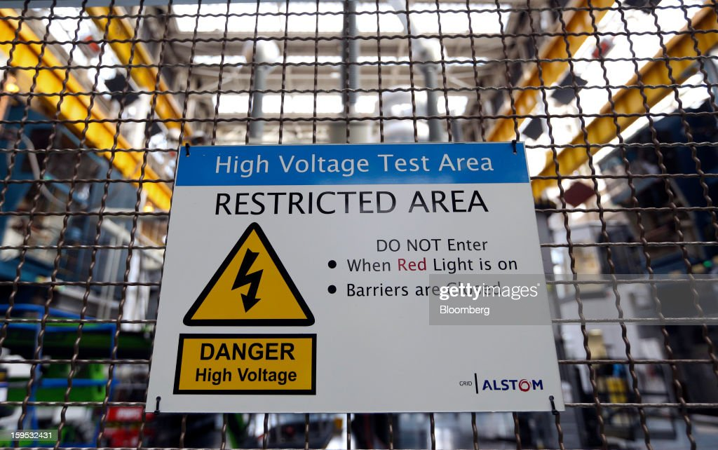 A sign warning of high voltage activity sits on a fence inside the industrial power transformer testing area at Alstom SA's factory in Stafford, U.K., on Tuesday, Jan. 15, 2013. Alstom surged 29 percent in Paris trading in 2012, beating the 15 percent gain of the the French benchmark CAC 40 Index. Photographer: Chris Ratcliffe/Bloomberg via Getty Images