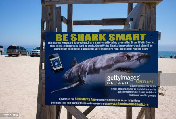 A sign warning of sharks offshore is fastened to a guard stand in East Orleans Massachusetts July 16 2017 Three attacks of great white sharks have...