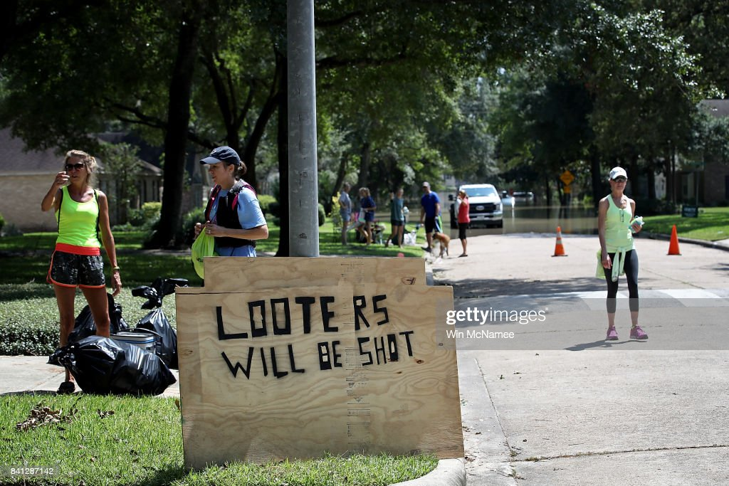 A sign warns looters in front of a home near the Barker Reservoir August 31, 2017 in Houston, Texas. The neighborhoods surrounding the reservoir are still experiencing severe flooding due to the accumulation of historic levels of rainfall, though floodwaters are beginning to recede in many parts of the city.